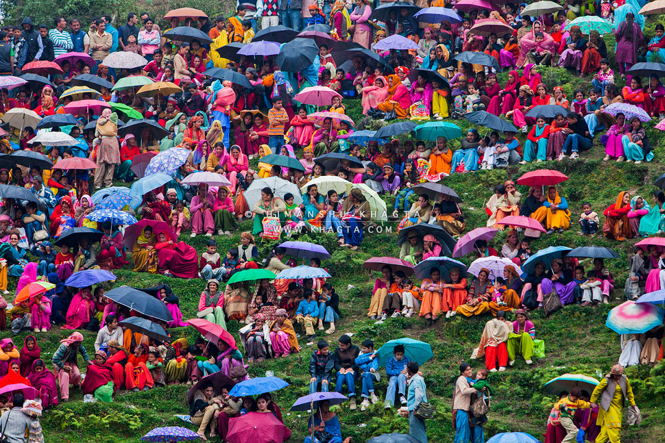 Women dressed in colorful clothes sitting on a hill slope, watching the annual wrestling event of Cheenj in Shimla